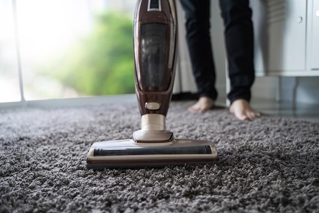 Gros plan homme à l'aide d'un aspirateur lors du nettoyage dans la chambre