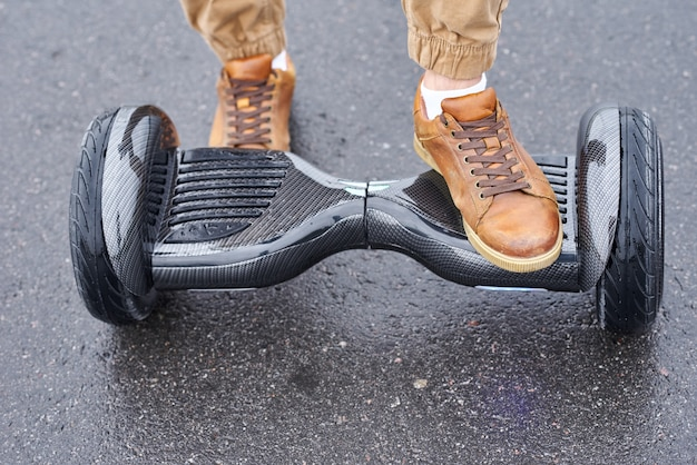 Gros plan de l'homme à l'aide de hoverboard sur route goudronnée. pieds sur scooter électrique extérieur