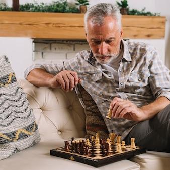 Gros plan, homme aîné, jouant aux échecs