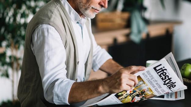 Gros plan, homme aîné, journal lisant