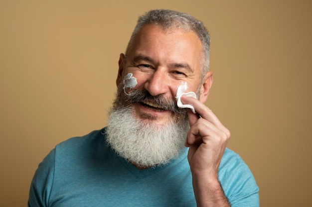 Gros plan homme appliquant la crème pour le visage