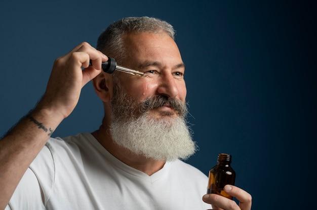 Gros plan homme appliquant le sérum pour le visage