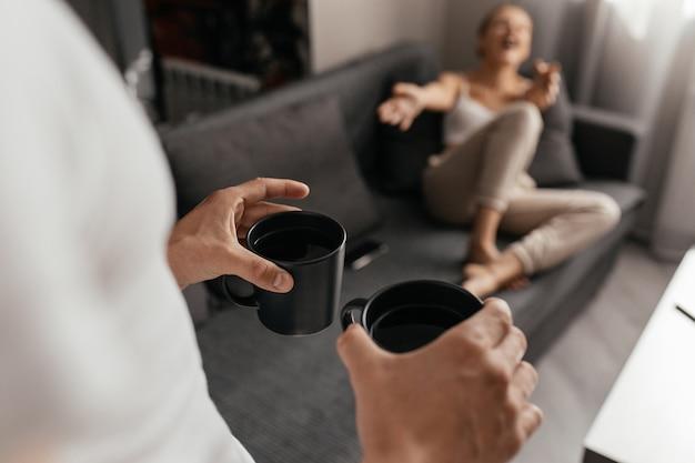 Gros plan sur l'homme apportant des tasses de thé à la femme allongée sur le canapé