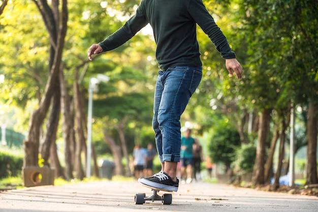 Gros plan homme asiatique jouant sur surfskate ou planche à roulettes dans un parc en plein air