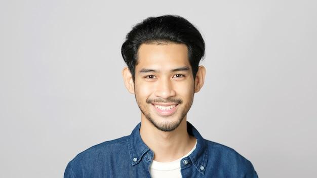 Gros plan d'un homme asiatique souriant et regardant la caméra en se tenant debout sur un fond gris isolé