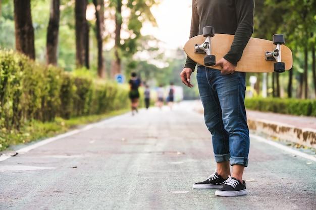 Gros plan de l'homme asiatique tenant le surfskate ou planche à roulettes dans le parc extérieur lorsque l'heure du lever du soleil