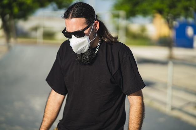 Gros plan d'un homme barbu dans une chemise noire portant un masque médical au parc