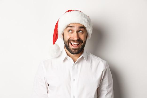 Gros plan d'un homme barbu heureux en bonnet de noel, célébrant noël et nouvel an et regardant dans le coin supérieur gauche, imaginer quelque chose. fond blanc.