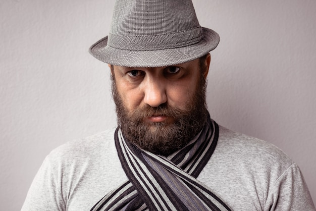 Gros plan d'un homme barbu portant un t-shirt gris clair, un chapeau et une écharpe sur fond gris