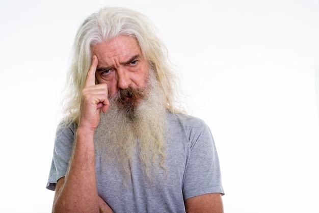 Gros plan d'un homme barbu senior pensant avec le doigt sur la tête