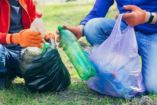 Gros plan sur un homme bénévole et son fils ramassant des ordures dans un parc et une forêt concept d'écologie les mains de deux personnes mettent une bouteille en plastique dans un sac poubelle