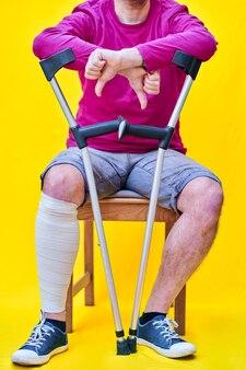 Gros plan d'un homme avec des béquilles, un jean et un t-shirt violet assis sur une chaise avec son pouce vers le bas.