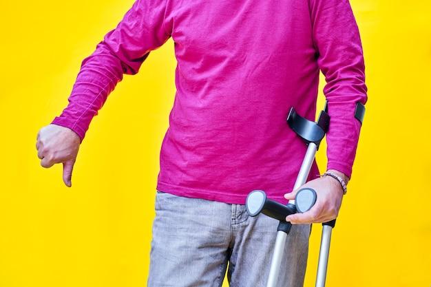 Gros plan d'un homme avec des béquilles, un jean et un t-shirt violet avec son pouce vers le bas.