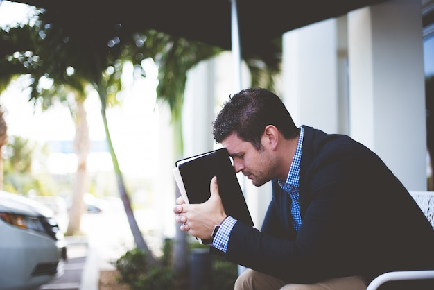 Gros plan d'un homme bien habillé assis tout en tenant la bible contre sa tête