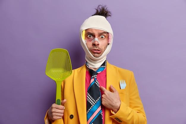 Gros plan sur un homme blessé avec une ecchymose sombre sous les yeux et une commotion cérébrale, porte un bandage