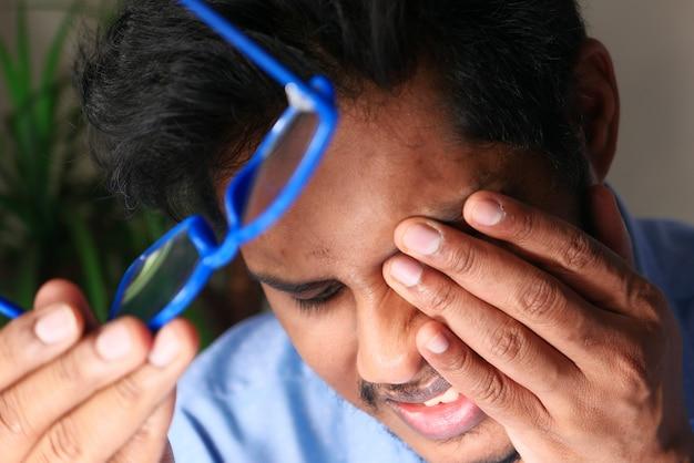 Gros plan d'un homme bouleversé souffrant de fortes douleurs oculaires.
