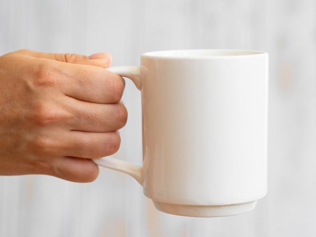Gros plan homme brandissant une tasse blanche