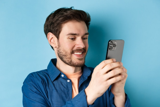 Gros plan d'un homme caucasien beau message d'écriture, lecture de l'écran mobile et souriant, debout sur fond bleu.