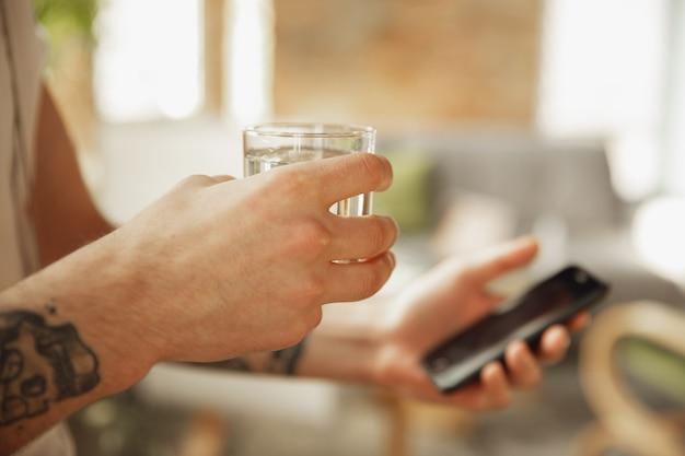 Gros plan d'un homme caucasien élégant utilisant un smartphone, prenant un selfie. surf, achats en ligne, défilement, paris, travail. concept d'éducation, d'indépendant, d'art et d'entreprise. boire du café.