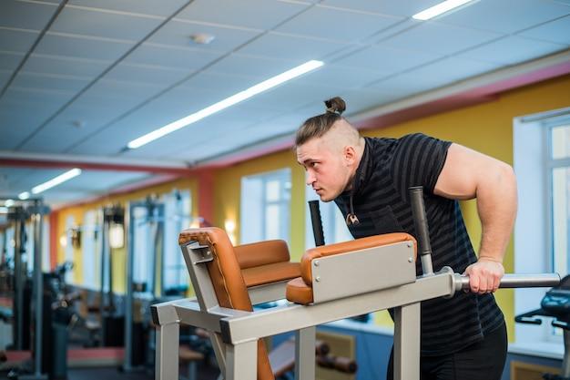 Gros plan sur l'homme concentré faisant des trempettes dans la salle de gym