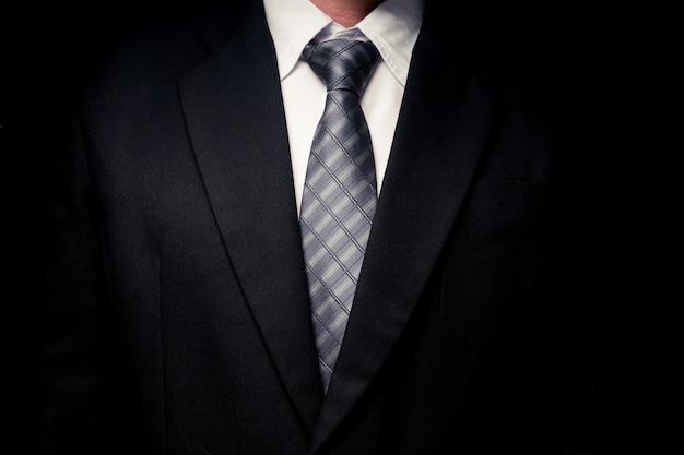 Gros plan de l'homme en costume noir, chemise et cravate sur fond noir