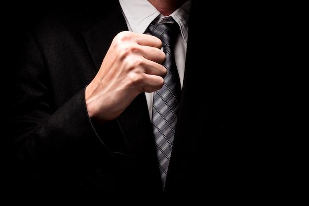 Gros plan de l'homme en costume noir avec le geste de la main sur fond noir.