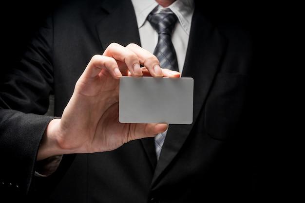 Gros plan de l'homme en costume noir, tenant la carte de visite sur fond noir