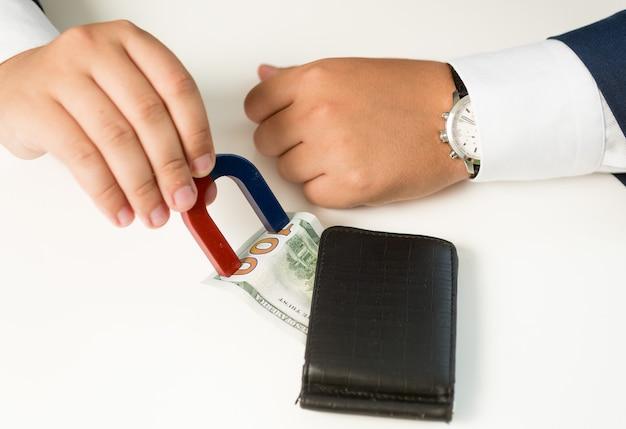 Gros plan d'un homme en costume tirant de l'argent sur un portefeuille avec un aimant