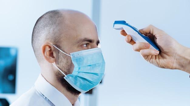 Gros plan sur l'homme dans un masque de protection mesure la température avec un thermomètre numérique