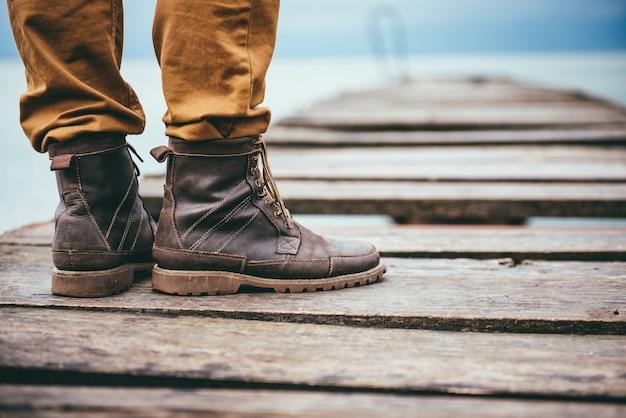 Gros plan, homme, debout, dock, porter, bottes cuir
