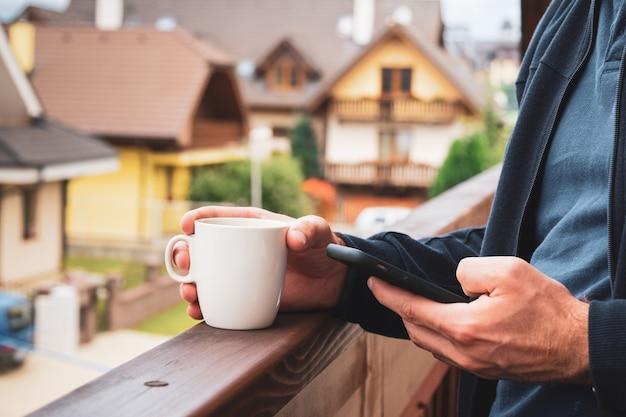 Gros plan homme debout avec une tasse blanche et à l'aide de son smartphone sur le balcon