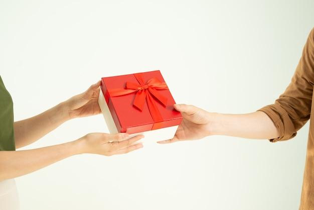 Gros plan, de, homme, donner, boîte cadeau rouge, à, femme, sur, mur blanc