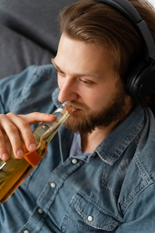 Gros plan, homme, à, écouteurs, et, boisson