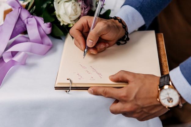 Gros plan d'un homme écrivant un message dans le livre d'or