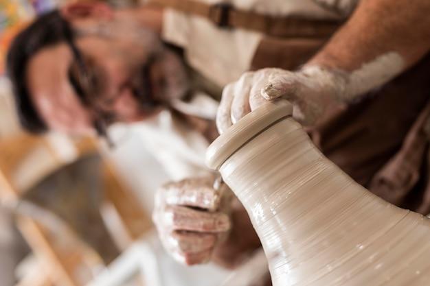 Gros plan homme faisant de la poterie