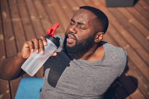 Gros plan sur un homme fatigué qui boit de l'eau