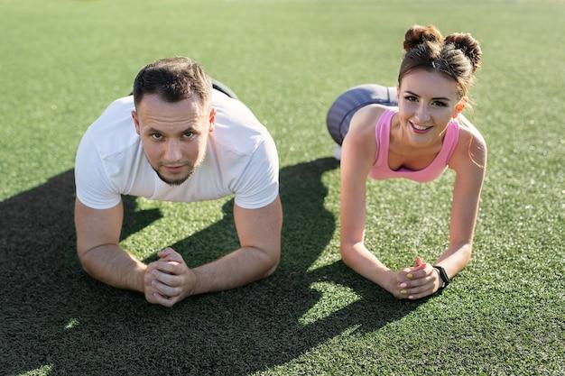 Gros plan d'un homme et d'une femme faisant un exercice de planche sur l'herbe dans un stade de sport au coucher du soleil