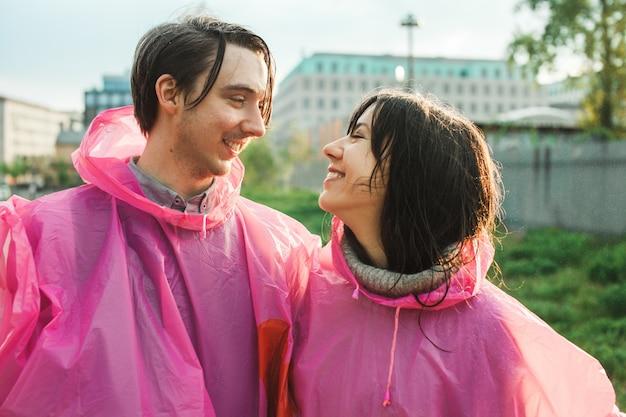 Gros plan d'un homme et d'une femme en imperméable en plastique rose souriant l'un à l'autre de façon romantique
