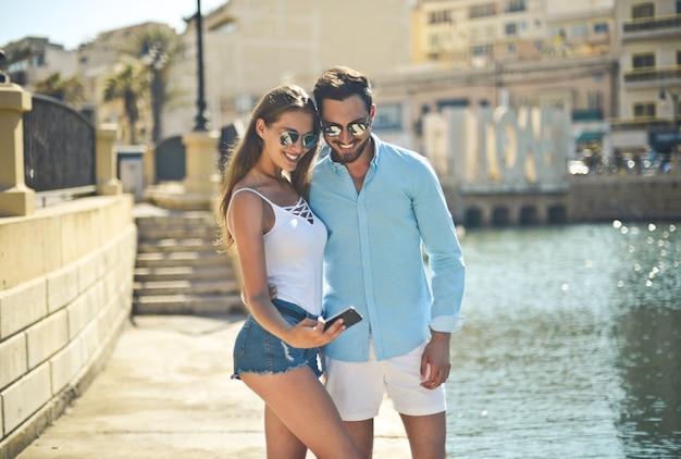 Gros plan d'un homme et d'une femme prenant un selfie dans la rue près d'une rivière