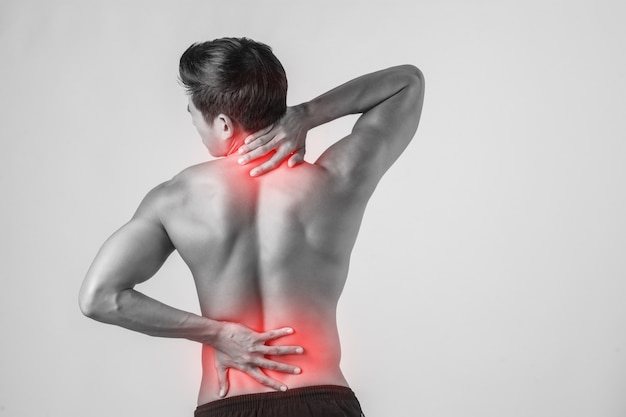 Gros plan de l'homme frottant son dos douloureux isolé sur fond blanc.