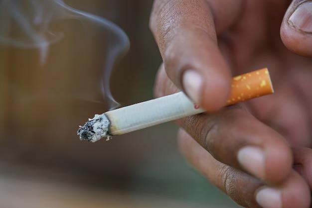 Gros plan homme fumer la cigarette à la main.