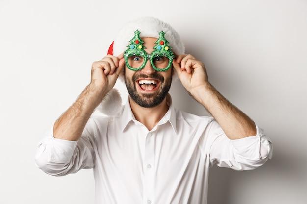 Gros plan d'un homme heureux célébrant les vacances de noël, portant des lunettes de fête et bonnet de noel, profitant du nouvel an, fond blanc.