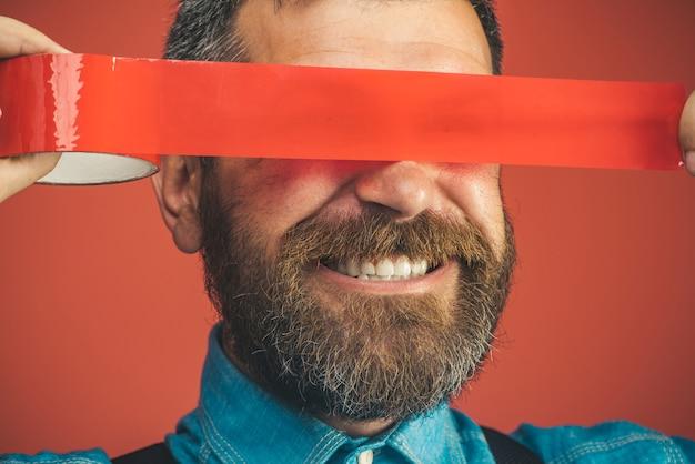 Gros plan homme heureux avec du ruban adhésif sur les yeux homme barbu souriant enveloppant du ruban isolant sur son