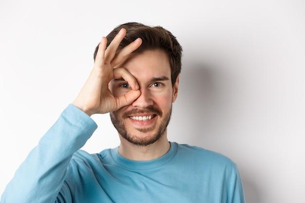 Gros plan sur un homme heureux regardant à travers le signe d'accord et souriant, approuvant et comme quelque chose de bien, debout sur fond blanc