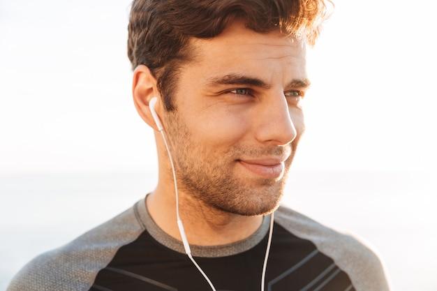 Gros plan d'un homme heureux en t-shirt, écouter de la musique via des écouteurs sans fil, lors d'une promenade en plein air au bord de la mer
