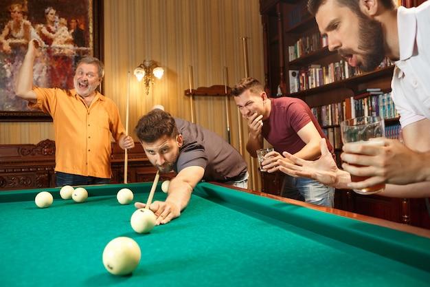 Gros plan d'un homme jouant au billard. le modèle caucasien vise soigneusement et vigoureusement par queue dans la balle. concept de jeu.