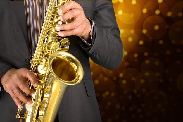 Gros plan homme jouant au saxophone sur fond doré flou