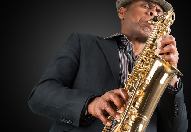 Gros plan homme jouant au saxophone sur fond