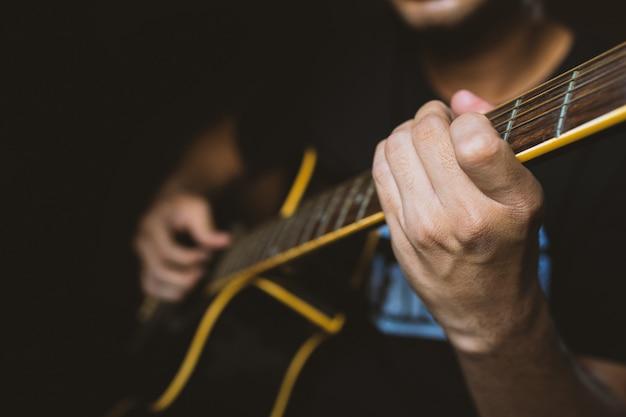 Gros plan de l'homme jouant de la guitare dans une pièce sombre