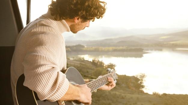 Gros plan, homme, jouer guitare
